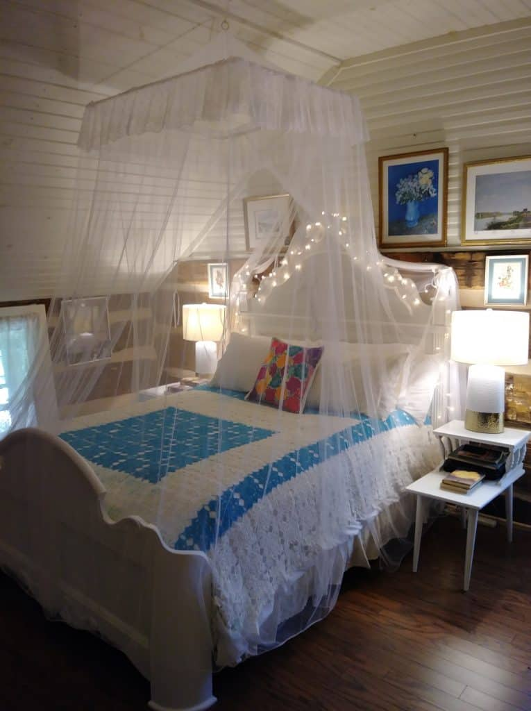 white bed with canopy and white lights