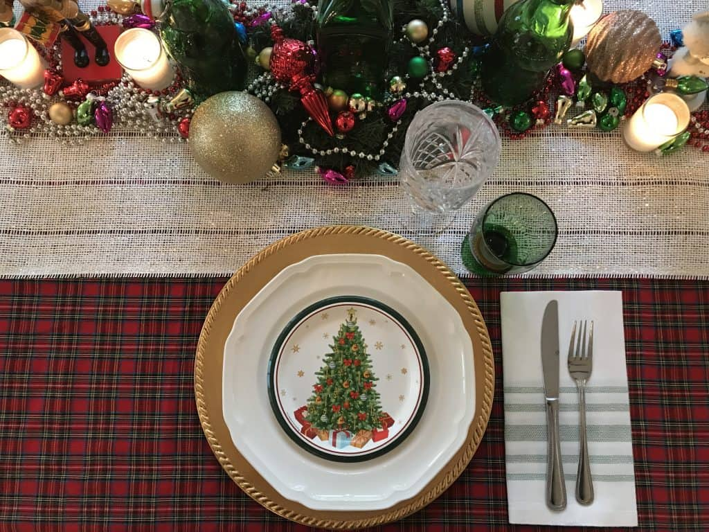 a Christmas table setting with festive decorations, beads, candles and a lovely place setting