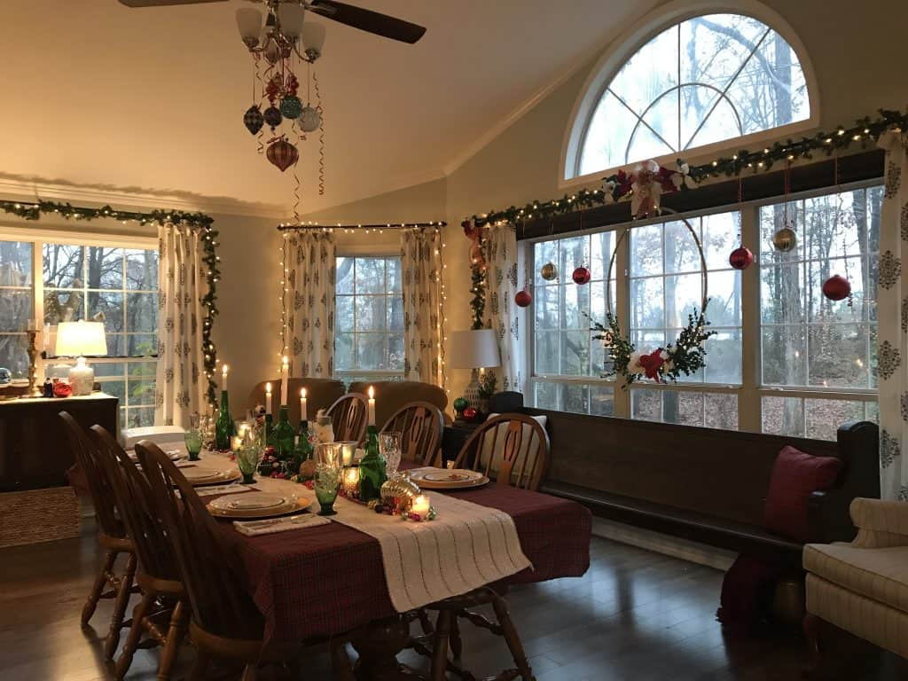 a dimly lit dining room with the glow of holiday lights and candles and ornaments hung from a ceiling fan