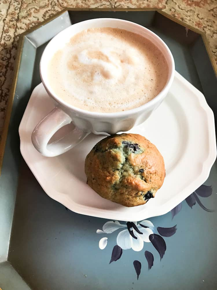 Life Full and Frugal / blueberry muffin on a painted blue tray with a frothy latte