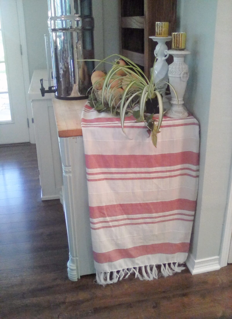 Creating Frugal Eclectic Fall Decor - Life Full and Frugal - cabinet with red and white striped table cloth draped over it, topped with Berkey water filter, plants and candles