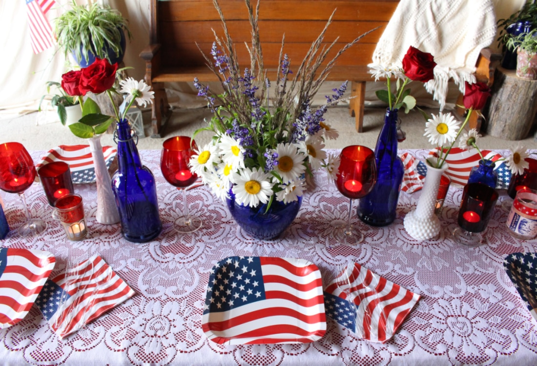 an arrangement of Shasta daisies and blue salvia on a 4th of July table life full and frugal