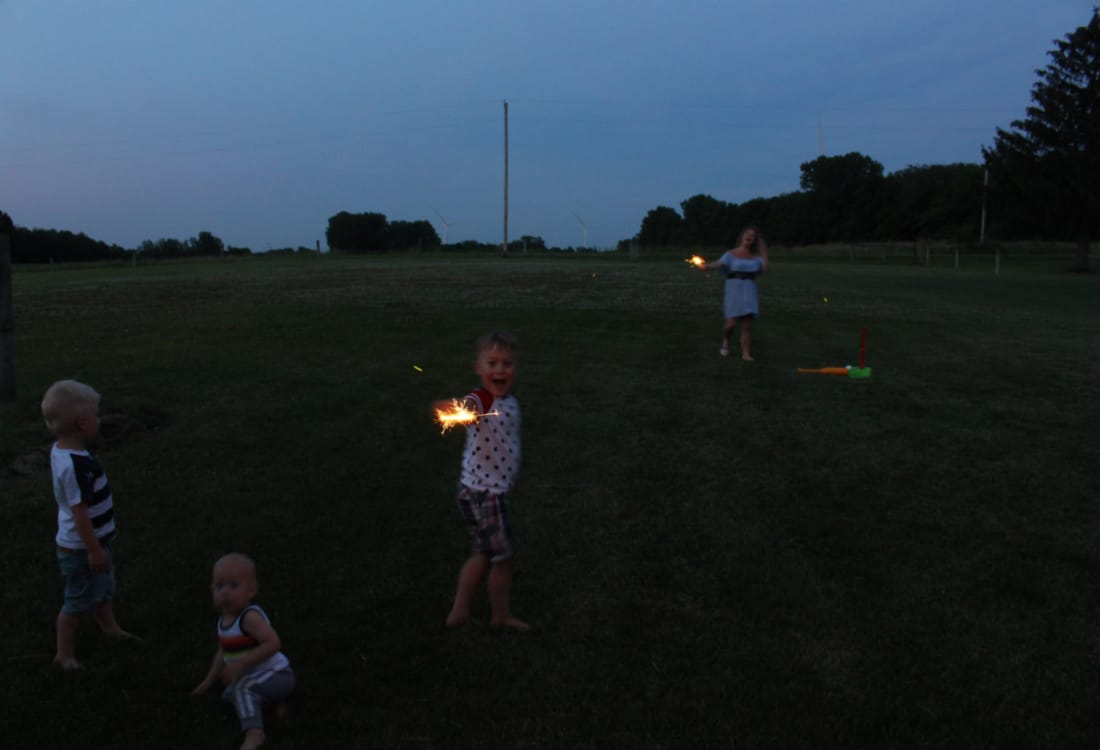 a little boy holding a sparkler for July 4th life full and frugal