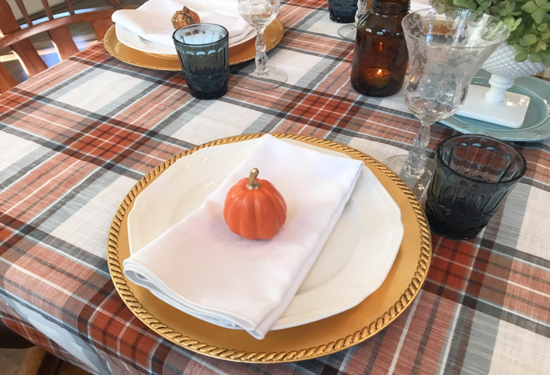 Creating Frugal Eclectic Fall Decor - Life Full and Frugal - fall table place setting with a plaid table cloth, gold charger, topped with white plate, white cloth napkin, and an orange ceramic pumpkin from the Target Dollar Spot