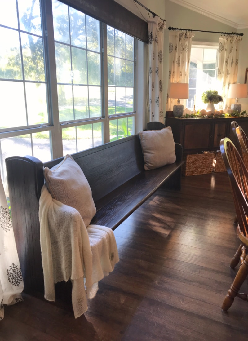 Creating Frugal Eclectic Fall Decor - Life Full and Frugal - dark stained church pew draped with a cozy blanket and big throw pillows