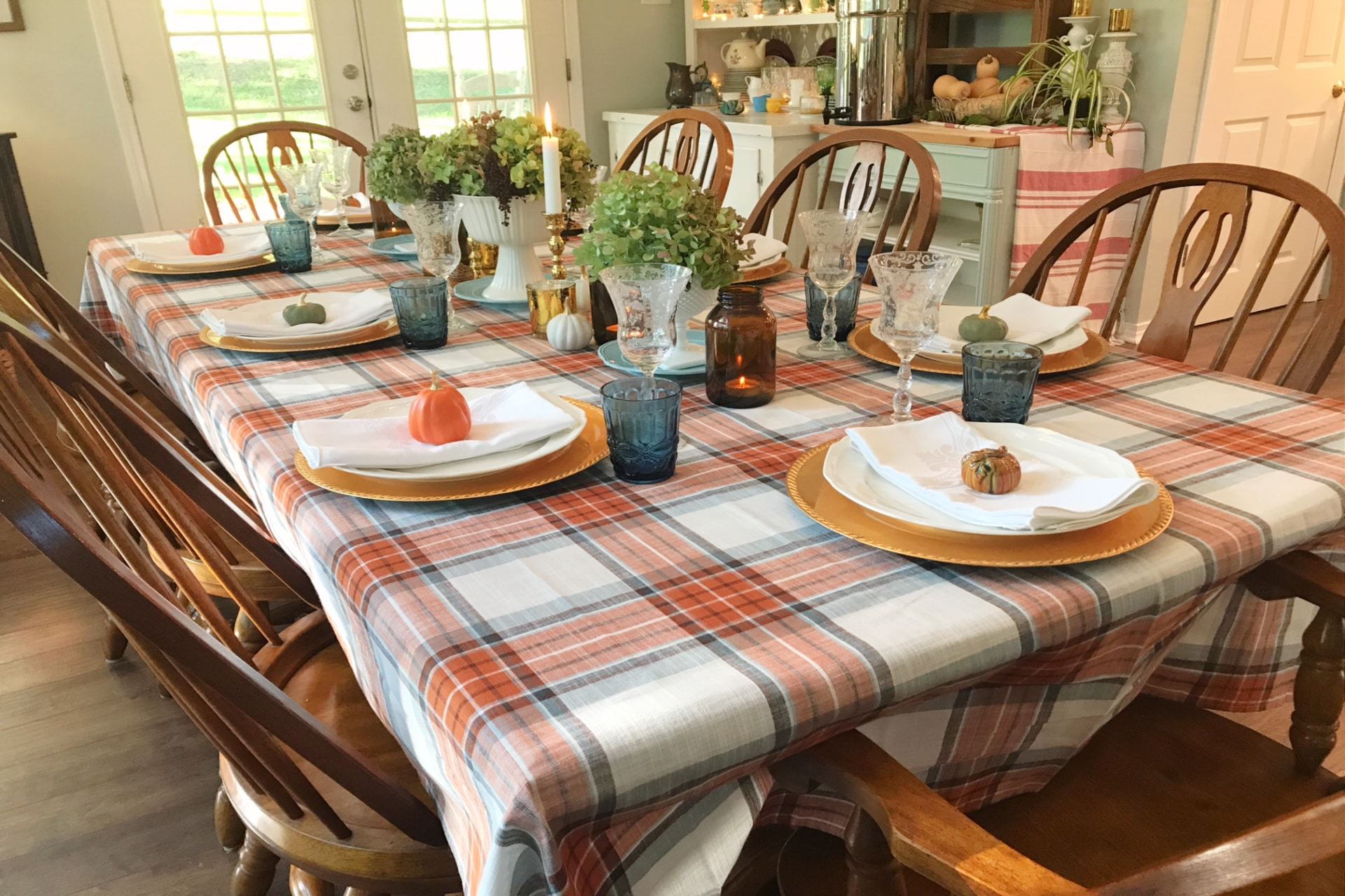 Creating Frugal Eclectic Fall Decor -table decorated for fall with plaid table cloth, gold chargers, white plates and napkins, vintage stemware, floral arrangements, ceramic pumpkins, Life Full and Frugal