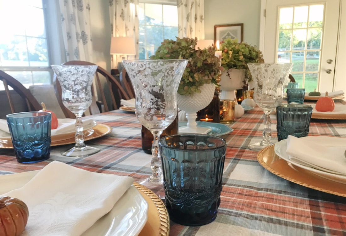 Creating Frugal Eclectic Fall Decor - Life Full and Frugal - table decorated for fall with a blue and orange plaid table cloth, patterned vintage stemware and blue pressed glass tumblers