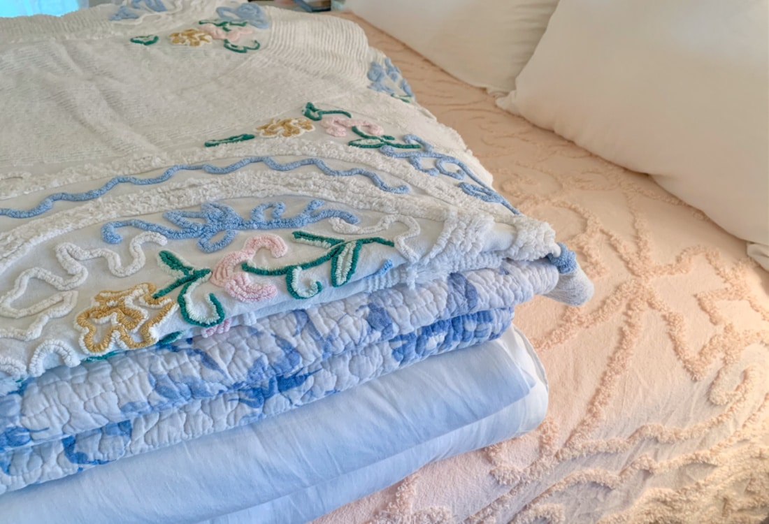 cotton blankets and quilts on a pink covered bed hygge home