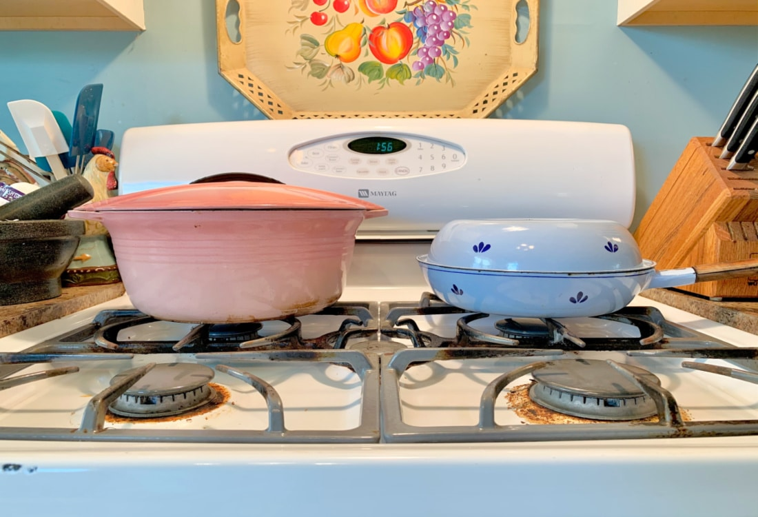 a pink and and a blue cast iron enamel pan on a stove hygge home
