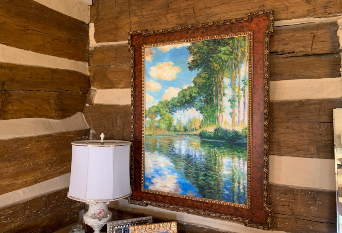 a copy of monet impressionist painting on a log cabin wall hygge home