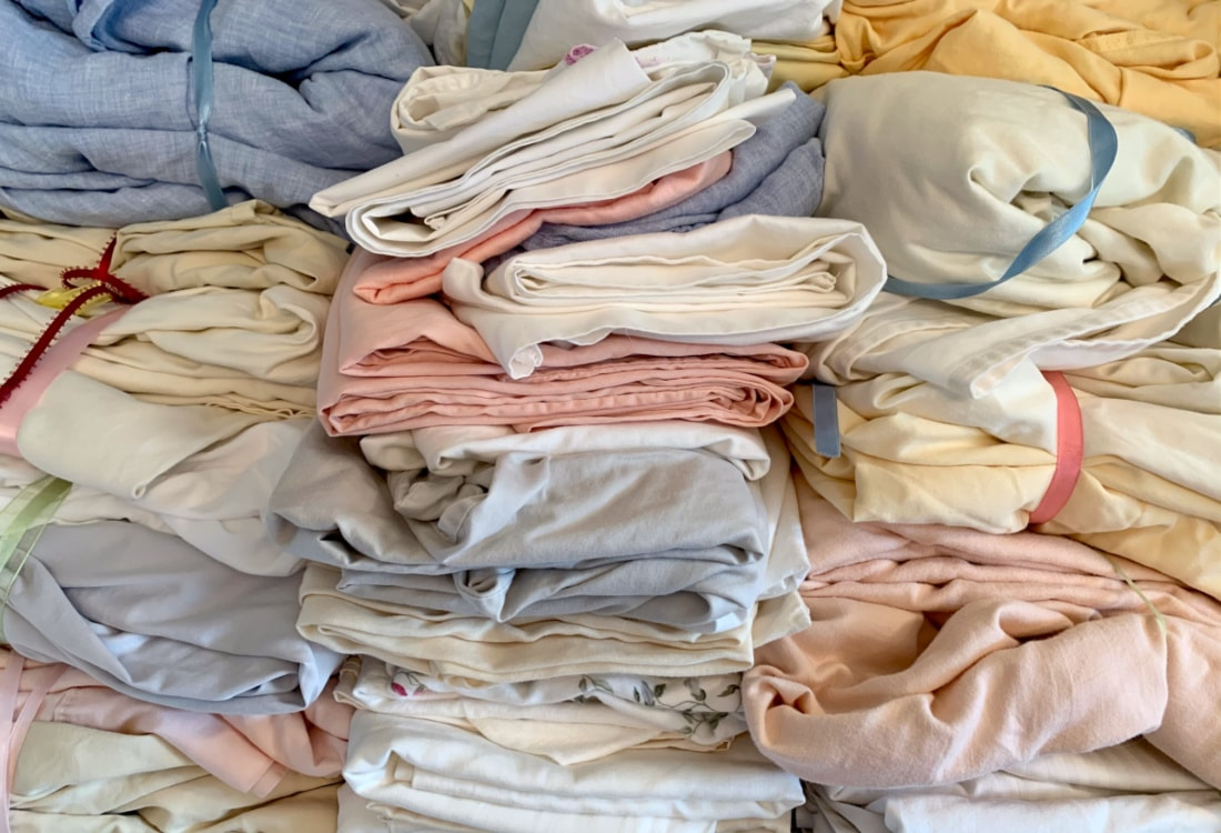 sets of cotton and linen sheets in a closet hygge home