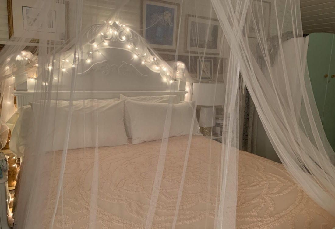 white lights over a canopy bed hygge home
