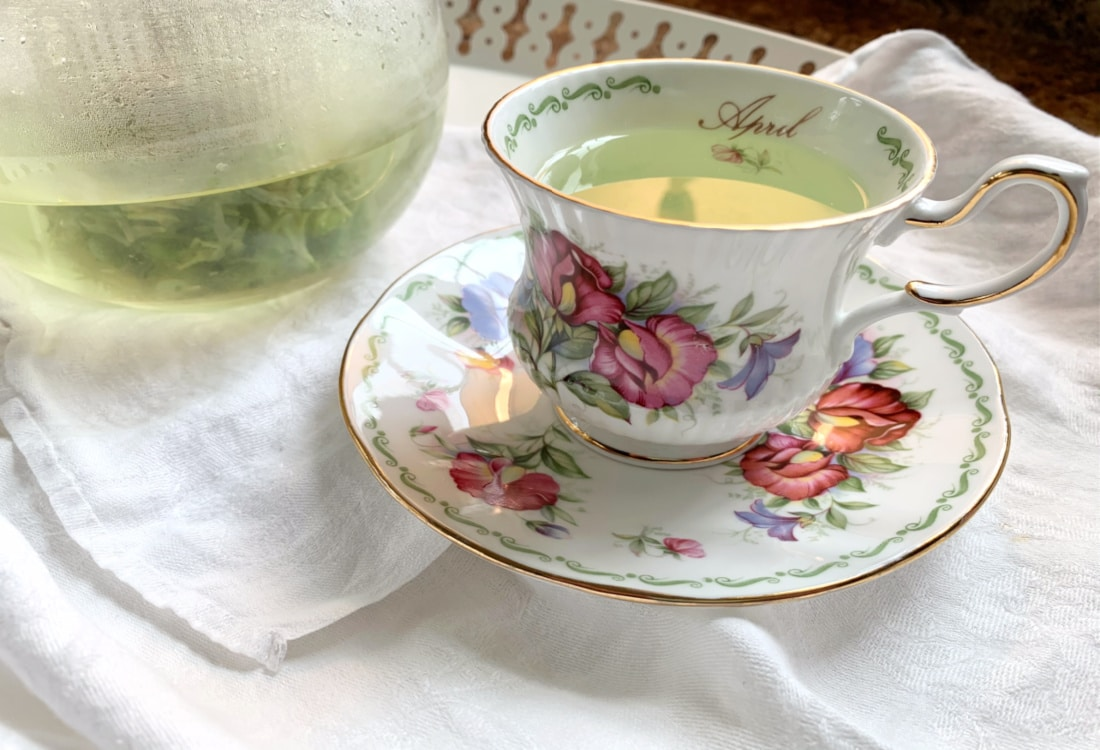 china tea cup with herbal infusion next to a clear tea pot of foraged herbal tea