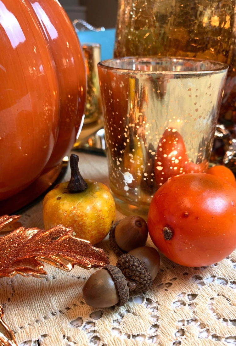fall table setting with ceramic pumpkin acorns gourds and gold mercury glass