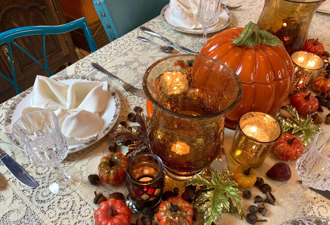 fall themed table with place settings candles gourds leaves and acorns